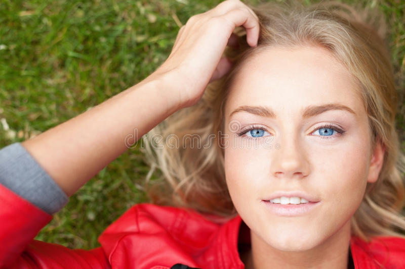 Beauty on the grass. Portrait of young beautiful woman laying on grass royalty free stock photos