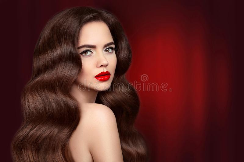 Beauty hair. Brunette girl portrait with red lips makeup and lon. G shiny wavy hair. Beautiful model with healthy hairstyle isolated on drapery curtains dark stock photography