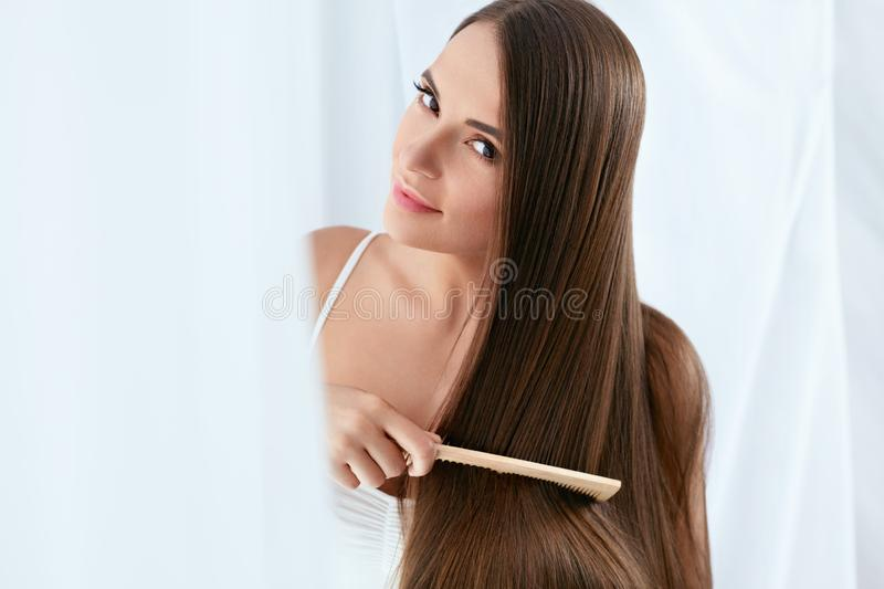 Beauty Hair Care. Beautiful Woman Combing Long Natural Hair. With Wooden Comb In White Interior. High Resolution stock photo