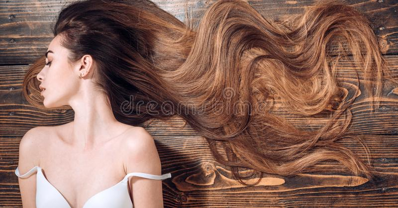 Beauty hair Salon. Woman with long beautiful hair. Fashion haircut. Beauty girl with long and shiny wavy hair. Trendy. Haircuts. Long healthy hair royalty free stock images