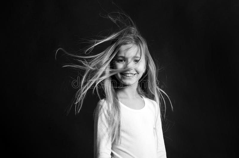 Beauty and hairdressing salon. Child model smiling with blowing long hair. Girl with adorable smile on dark background royalty free stock photos