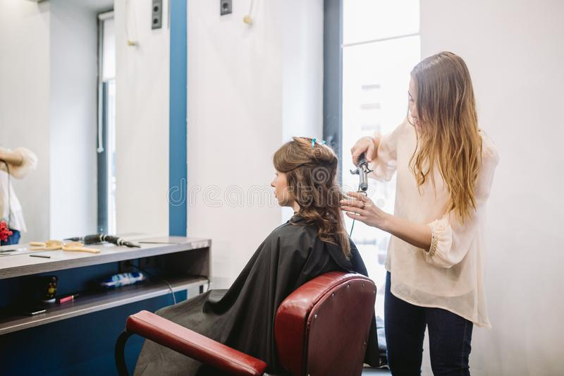 Beauty, hairstyle concept, happy young woman and hairdresser with hair iron making hairdo at hair salon. Woman Having royalty free stock images