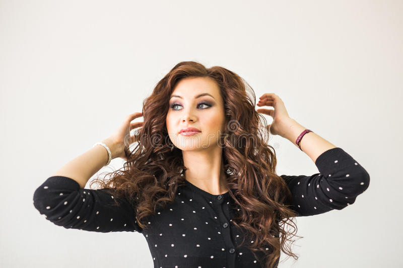 Beauty, hairstyle and people concept - happy young woman with finishing hairdo at salon. royalty free stock photography