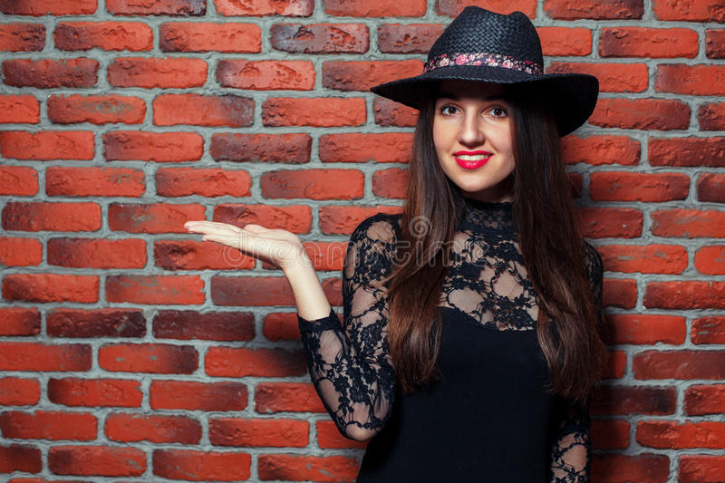 Beauty in the hat. Portrait of a young beautiful girl in black body dresses on the background of a brick wall royalty free stock images
