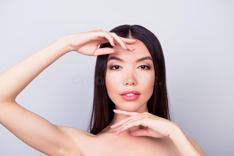 Beauty, health woman concept. Young pretty chinese lady is touching gently her attractive healthy skin of the face with fingers. Pretty attractive lady stock photography