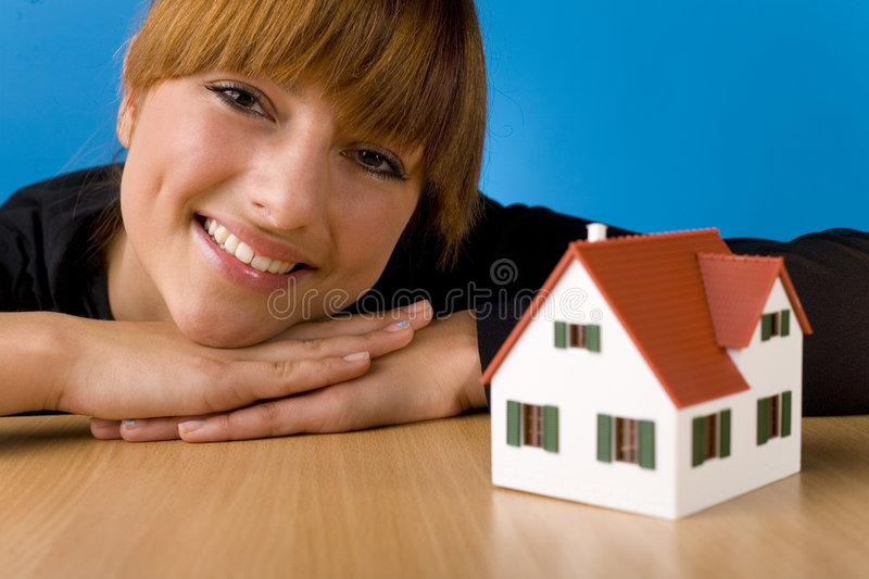 Beauty and house miniature. Beautiful woman lying on desk in front of house miniature. Smiling and looking at camera. Front view, blue background royalty free stock photography
