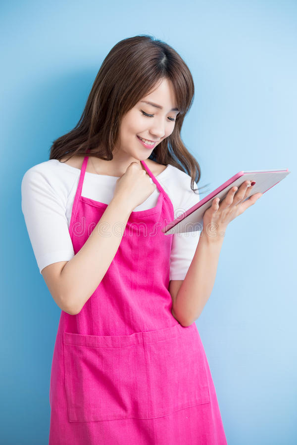 Beauty housewife take tablet. And smile on blue background, asian stock photo