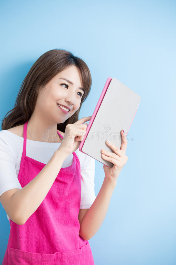 Beauty housewife take tablet. And smile on blue background, asian stock photos