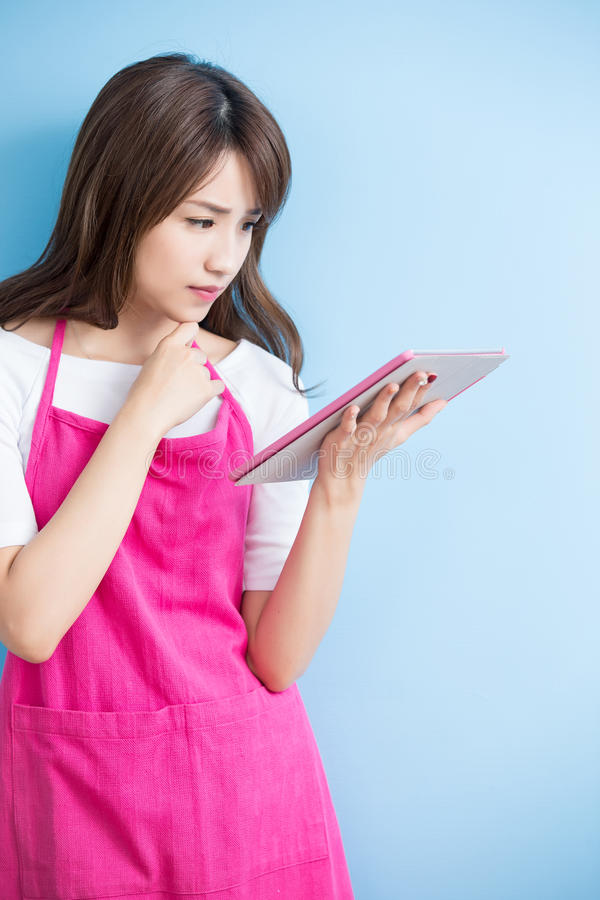 Beauty housewife take tablet. And smile isolated on blue background, asian royalty free stock photography