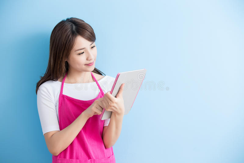 Beauty housewife take tablet. And smile isolated on blue background, asian royalty free stock image