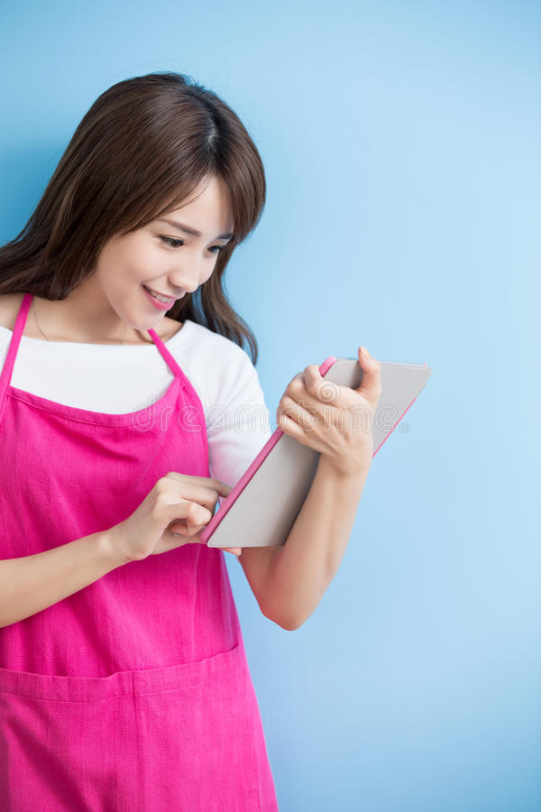Beauty housewife take tablet. And smile isolated on blue background, asian royalty free stock photo