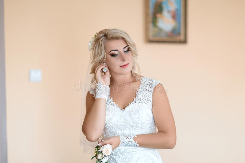 Beauty and jewelery concept - woman wearing shiny diamond earrings, the bride wears earrings, in a white wedding dress and gloves stock photography