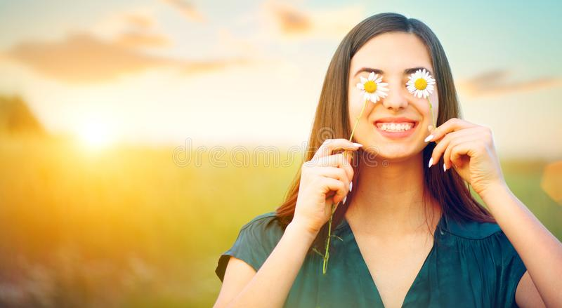Beauty joyful girl with daisy flowers on her eyes enjoying nature and laughing on summer field royalty free stock image