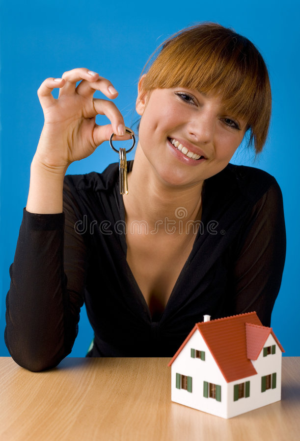 Beauty with keys. Beautiful woman sitting at desk in front of house miniature. Holding keys. Smiling and looking at camera. Front view, blue background stock photography