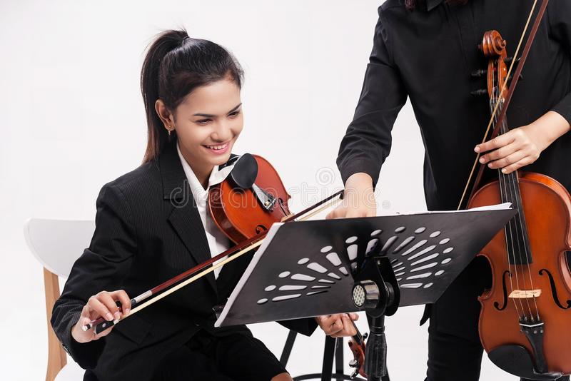 The beauty lady in black uniform is study violin by the teacher,she is looking at note that the teacher teaching,at studio music r royalty free stock photos