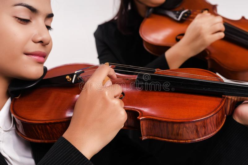 The beauty lady is playing viloin by press the finger to the string and strap,the Pizzacato technic. Blurry light around royalty free stock image