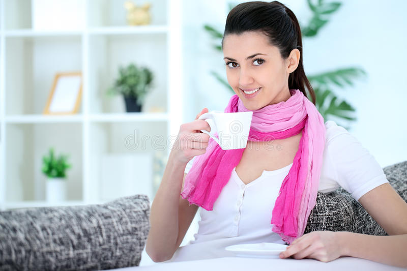 Beauty lady sitting on sofa and drinking coffee stock photo