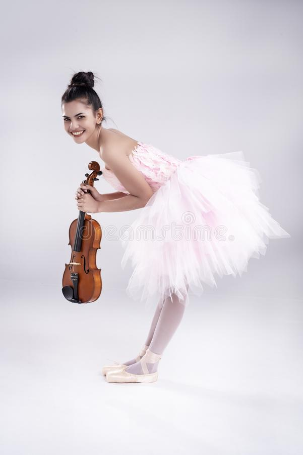 The beauty lady is wearing pink ballet dress, stand and bend body down,hold violin in hand,with smile and happy face, royalty free stock photo