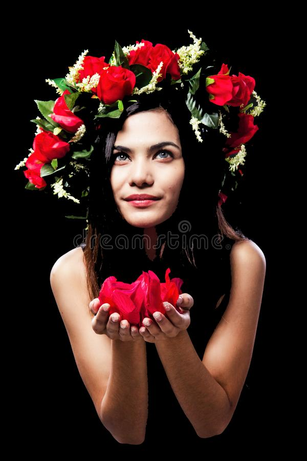 The beauty lady is wearing rose crown on her head,rose petals in hands royalty free stock photography