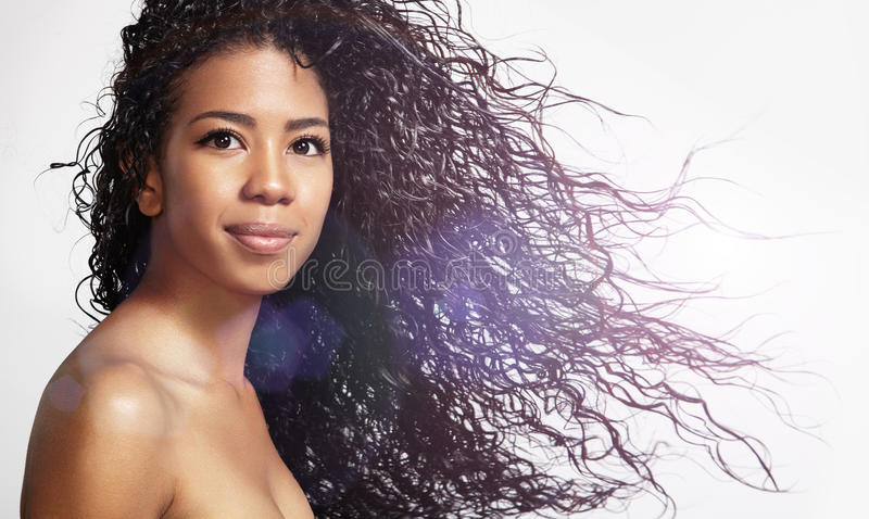 Beauty latin woman with curly hair. Happy black woman with blowing curly hair stock photos