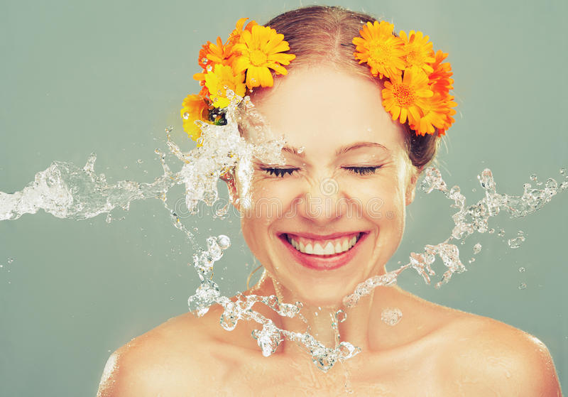 Beauty laughing girl with splashes of water and yellow flowers stock photos