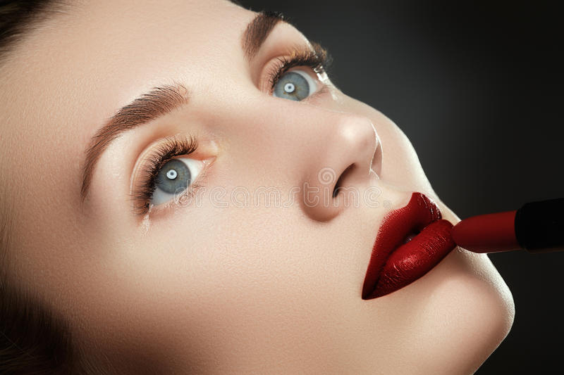 Beauty lips. Beautiful lips close-up, great idea for the advertising of cosmetics. Model applying red lipstick. Makeup. Professional fashion retro make-up. Red royalty free stock photo