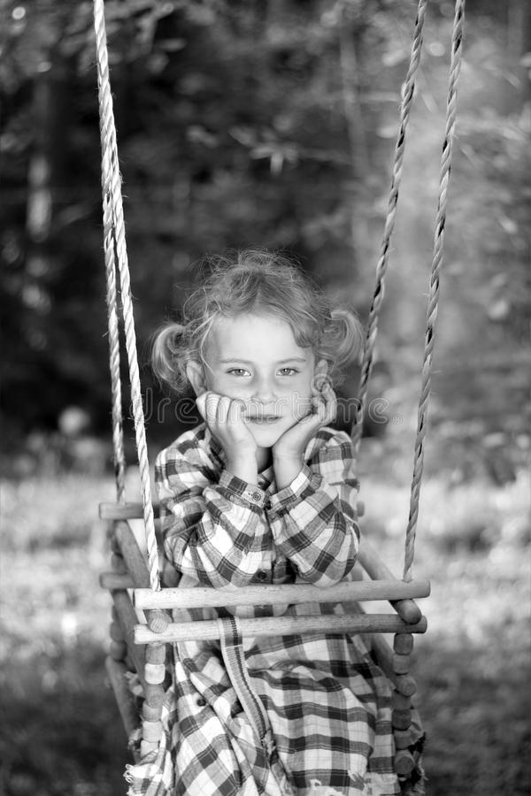 Beauty little girl on a swing stock photos