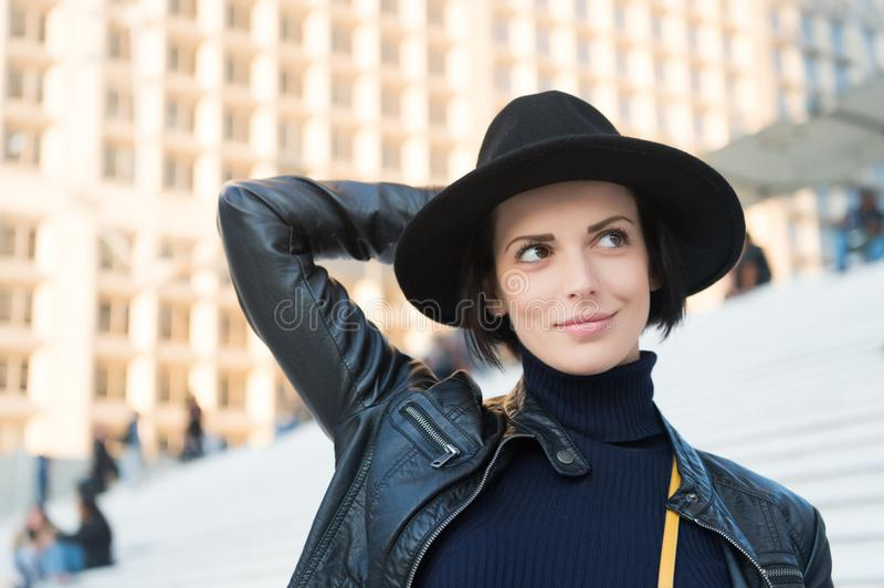 Beauty, look, makeup. Woman in black hat smile on stairs in paris, france, fashion. Fashion, accessory, style. Sensual woman with. Brunette hair, hairstyle royalty free stock photo