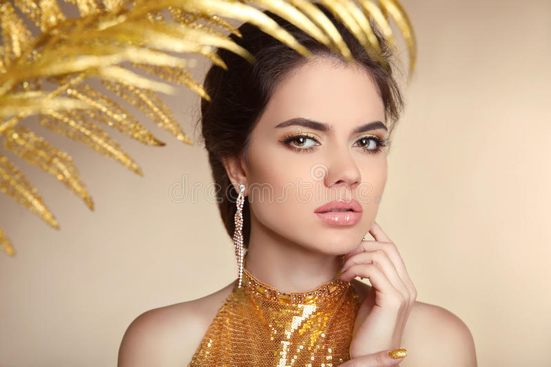 Beauty make-up. Beautiful girl model. Golden luxury Jewelry.Manicured nail. Fashion art photo of young woman isolated on beige ba. Ckground royalty free stock image