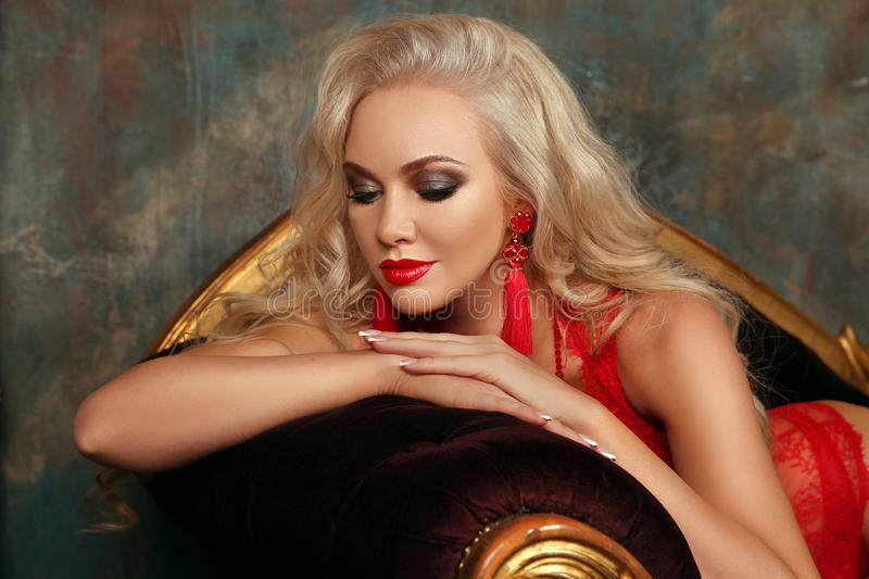 Beauty makeup. Beautiful fashion blond girl model with red lips, fashion earrings, blonde wavy hair style, french manicured nails royalty free stock photos