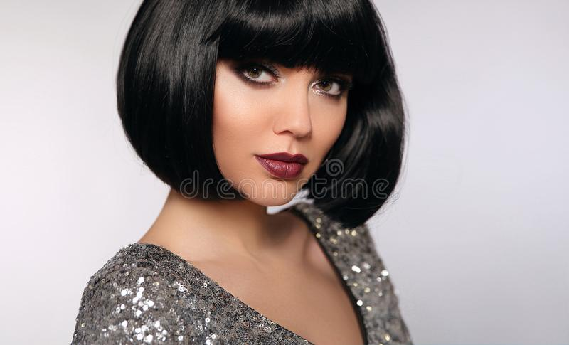 Beauty Makeup, Bob hairstyle. Fashion Style Brunette Woman Portrait with black Short Hair and glitter lips isolated on gray stock image