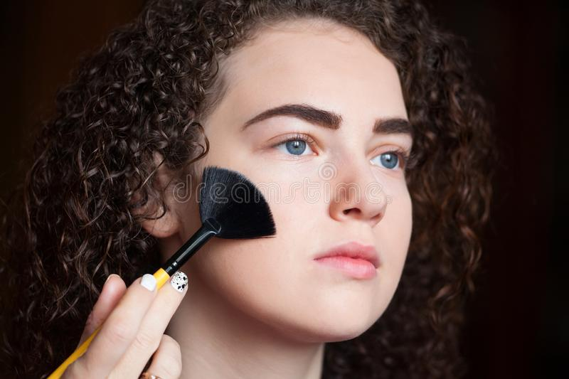 Closeup portrait of beautiful woman getting professional make-up with brush royalty free stock photo