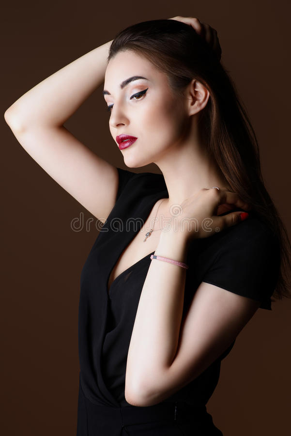 Young woman posing. Beauty and makeup concept. Portrait of a beautiful brunette woman with perfect skin and bright makeup. Eyeliner, arrows stock photos