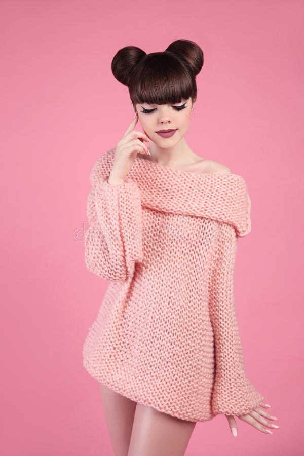 Beauty makeup. Fashion teen girl model. Brunette with matte lips. And hairstyle wearing soft sweater posing over studio pink background royalty free stock photography