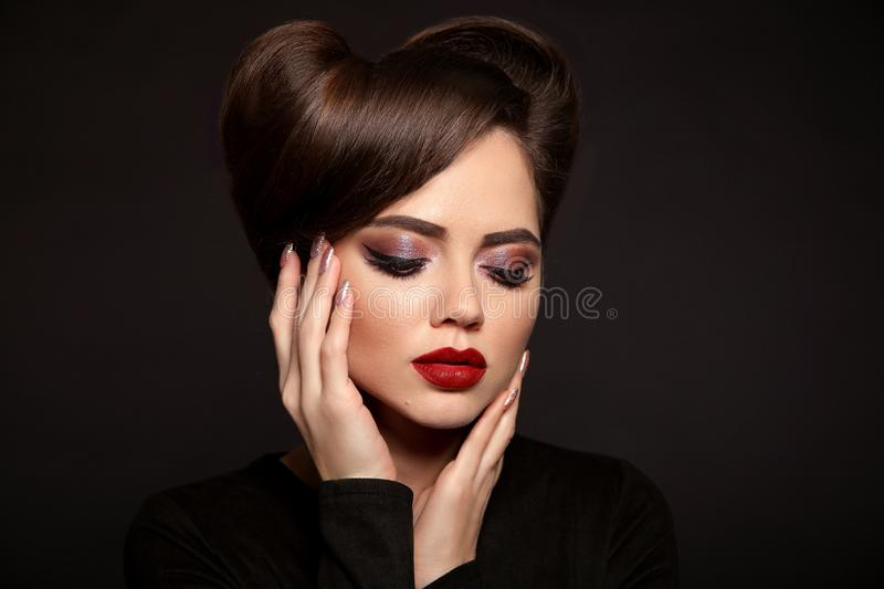 Beauty Makeup and Hairstyle. Beautiful woman with red lipstick, long eyelashes, glitter eye shadow and retro hair style, royalty free stock photography