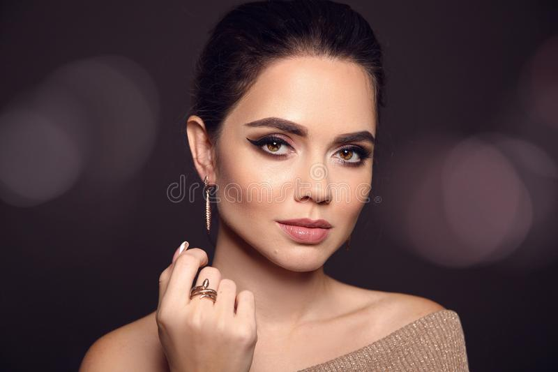 Beauty Makeup Portrait. Fashion Model Golden Jewelry. Beautiful royalty free stock photography