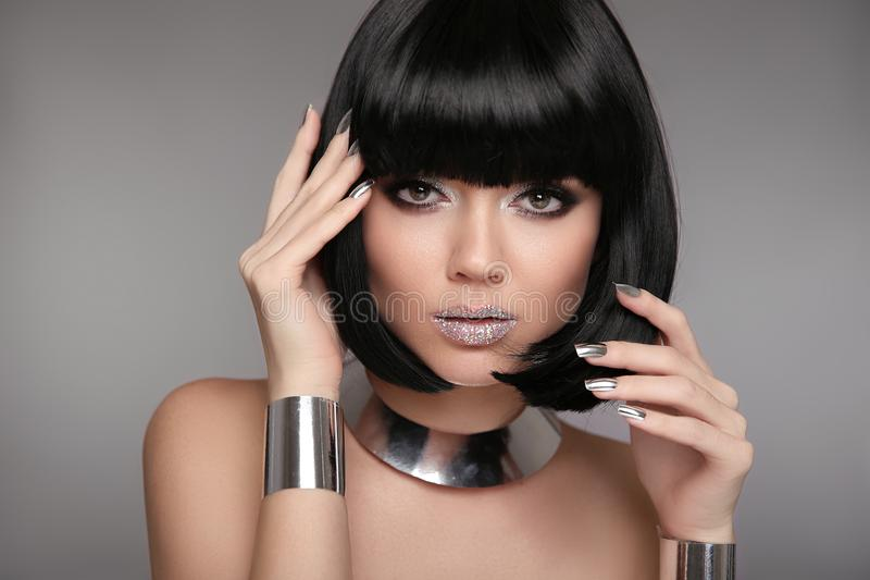 Beauty Makeup, Silver Manicured polish nails. Bob hairstyle. Fashion Style Brunette Woman Portrait with black Short Hair and. Glitter lips isolated on gray stock photo
