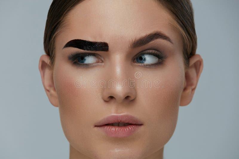 Beauty makeup. Woman coloring eyebrow with brow gel tint. Beauty makeup. Woman coloring eyebrow with gel tint closeup. Girl model setting liquid peel-off brow royalty free stock image