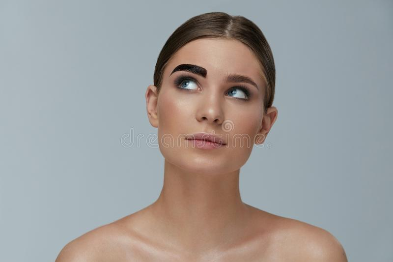 Beauty makeup. Woman coloring eyebrow with brow gel tint. Beauty makeup. Woman coloring eyebrow with gel tint portrait. Girl model setting liquid peel-off brow royalty free stock photo