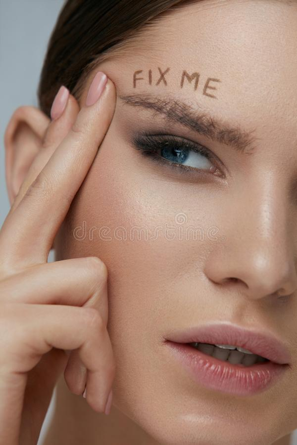 Beauty makeup. Woman face with messy eyebrow and fix me on skin. Beauty makeup. Woman face with messy eyebrow and fix me sign on skin closeup. Girl model with stock image
