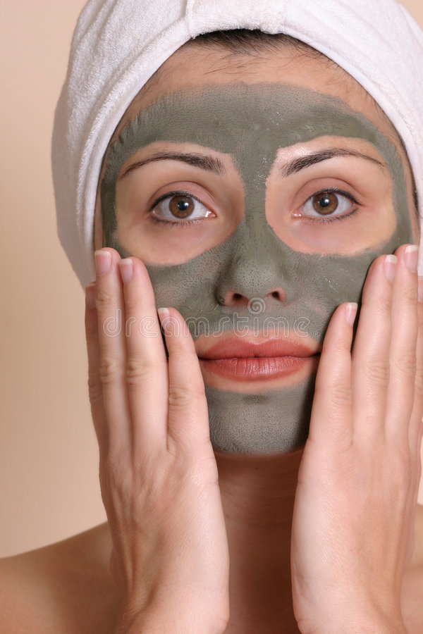 Beauty Mask. Woman with a green clay mud beauty mask applied to her face royalty free stock image