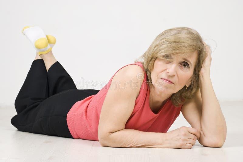 Beauty mature woman posing on floor stock photography