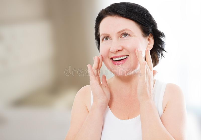 Beauty middle age woman face portrait. Spa and anti aging concept at home background. Plastic surgery and collagen. Wrinkles royalty free stock photo