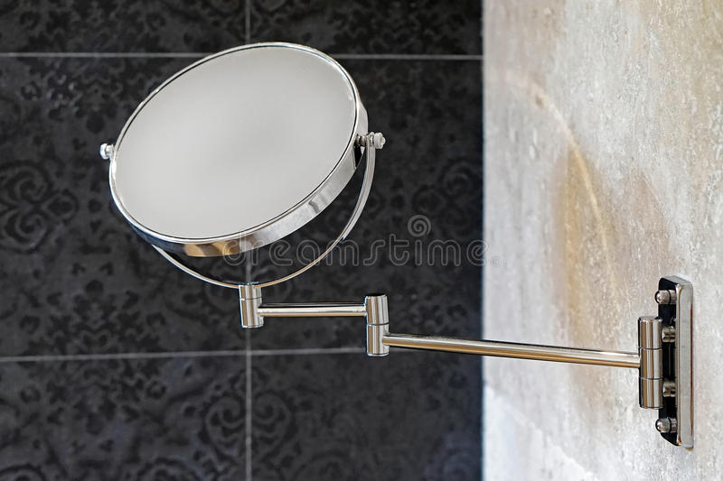 Beauty mirror. Double sided round makeup beauty mirror at wall in bathroom royalty free stock photography
