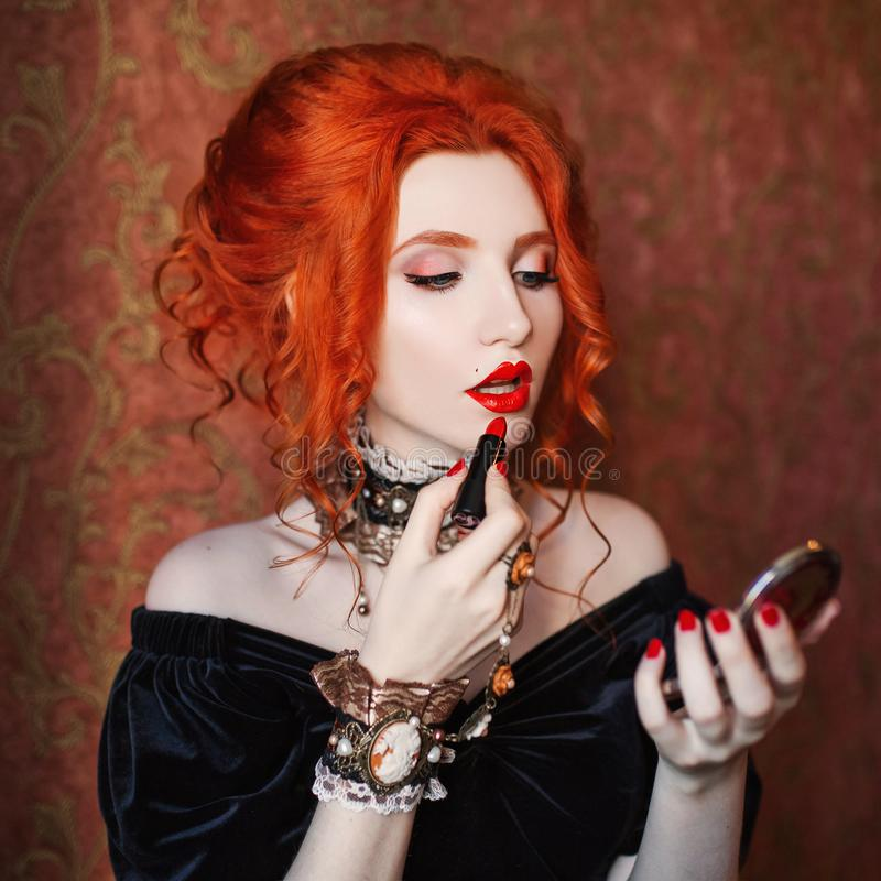 Beauty model dye lips. Halloween attire. woman is vampire with pale skin and red hair. Girl witch dye lips with red lipstick. Gothic outfit for halloween stock photography