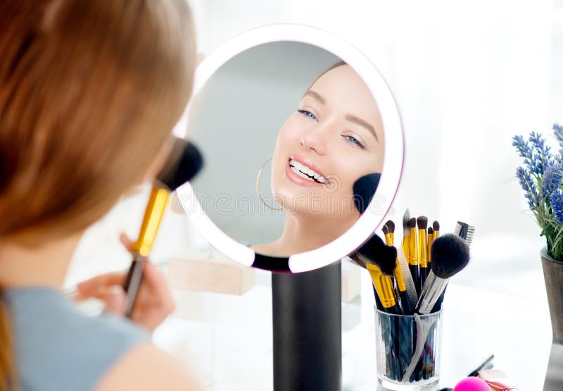 Beauty model girl applying makeup. Beautiful young woman looking in the mirror and applying cosmetic with a big brush. Smiling girl gets blush on the stock photos