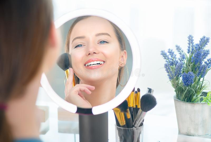 Beauty model girl applying makeup. Beautiful young woman looking in the mirror and applying cosmetic with a big brush. Smiling girl gets blush on the royalty free stock image