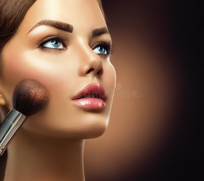 Beauty model girl applying makeup royalty free stock images