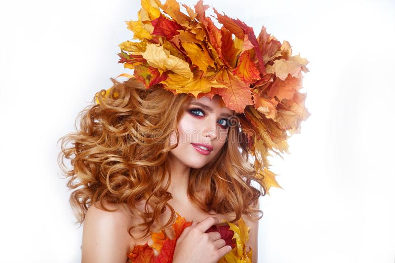 Beauty model girl with autumn bright leaves hairstyle. Beautiful Fashion female with Autumnal Make up and Hair style. stock photography