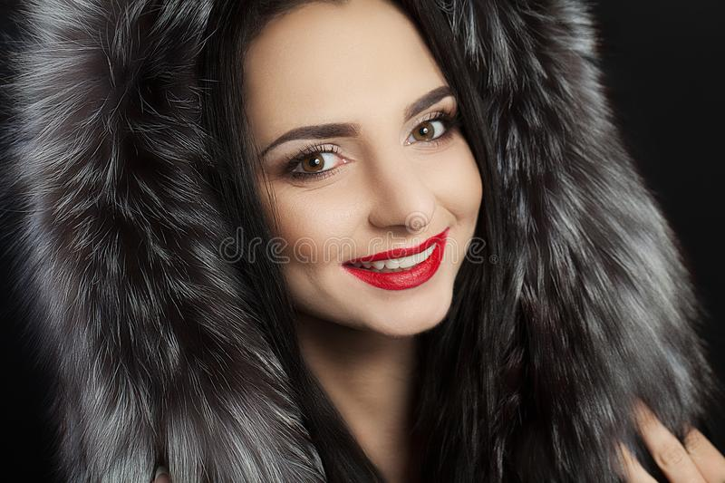 Beauty is a model girl in a black fur coat. Beautiful winter luxury woman. Photographed photo. Professional makeup. Red lips. Youn stock images
